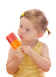 Little girl eating colorful ice lolly. Isolated on white background Royalty Free Stock Image