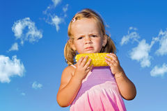 Little girl eating cooked sweet corn Stock Image