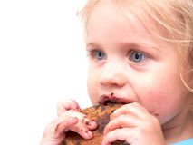 A little girl eating a cookie. Isolated on white Royalty Free Stock Images