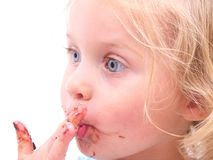 A little girl eating a cookie. Isolated on white Stock Photography