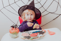 Little girl eating cookies on halloween Royalty Free Stock Photos