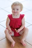 Little girl eating cookies sitting on the floor Stock Images