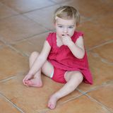 Little girl eating cookies sitting on the floor Royalty Free Stock Image