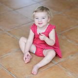 Little girl eating cookies sitting on the floor Royalty Free Stock Photography