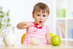 Little girl eating cornflakes with milk in home. Little girl eating cornflakes with milk at table in home Royalty Free Stock Photos