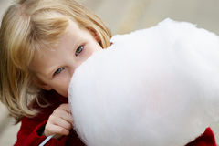 Little girl eating cotton candy. Little girl in a red sweater eating cotton candy Stock Image