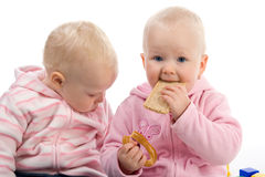 Little girl eating a cracker. Little girls sit on the floor Stock Photo