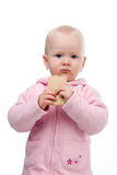 Little girl eating a cracker. The little girl in a pink jacket hold in her hand cracker Royalty Free Stock Photography