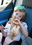 Little girl eating a croissant with chocolate in the car Royalty Free Stock Images