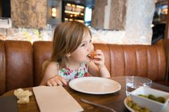 Little girl eating croquette with hand in restaurant. Four years age blonde girl eating croquette with hand next to woman mother sitting in brown leather sofa at stock photos