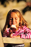 Little girl eating a cupcake stock photos