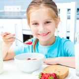 Little girl eating. Cute little girl eating cereal and strawberries in the kitchen royalty free stock photo