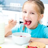 Little girl eating. Cute little girl eating cereal and strawberries in white kitchen Stock Photography