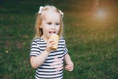 Little girl eating delicious ice cream. In the summer. The concept of family recreation. Toning royalty free stock photo