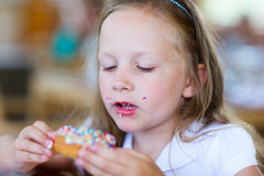 Little girl eating donut Royalty Free Stock Photos