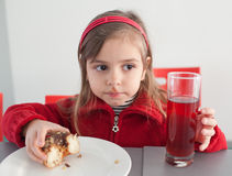 Little girl eating donut with juice Stock Photos