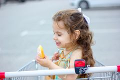 Little girl eating a donut at mall parking. Stock Images