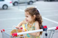 Little girl eating donuts at mall parking outdoor. Little girl eating donuts at mall parking outdoor Royalty Free Stock Image