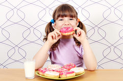Little girl eating donuts Royalty Free Stock Photography