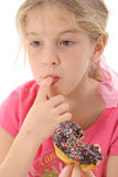Little girl eating a doughnut Royalty Free Stock Images