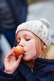 Little girl eating egg Stock Images