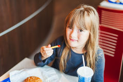 Little girl eating fast food in a cafe. Chips, hamburger and drink stock photos