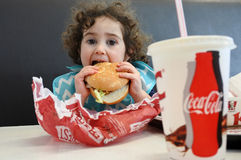 Little girl eating fast food Stock Photos
