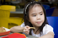 Little Girl Eating French Fries Stock Photos