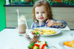 Little girl eating french fries in a restaurant. Royalty Free Stock Image