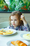 Little girl eating french fries in a restaurant. Stock Image