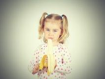 Little girl eating a fresh banana. Royalty Free Stock Image