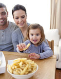 Little girl eating fries at home Stock Photos