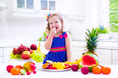 Little girl eating fruit Royalty Free Stock Images
