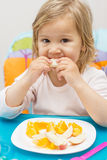 Little Girl Eating Fruit Stock Photography