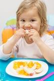 Little Girl Eating Fruit Stock Photography