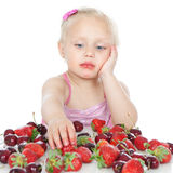 Little girl eating fruit on white Royalty Free Stock Image