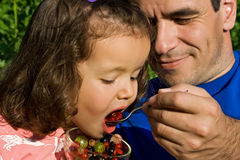 Little girl eating fruits Stock Images