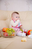 Little girl eating fruits Stock Photos