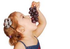 Little girl eating grape. Studio shot Stock Images