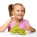 Little girl is eating grapes. Isolated over white stock image