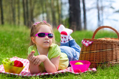 Little girl eating grapes at picnic Stock Images