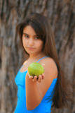 Little girl eating a green apple. A portrait of a little girl holding a green apple (focus on the apple Stock Photography
