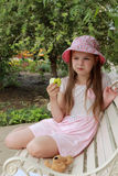 Little girl eating green apple Stock Image