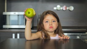 Little girl eating a green apple and smiling stock footage