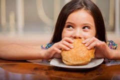 Little girl eating a hamburger Stock Image