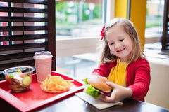 Little girl eating a hamburger in fast food restaurant Royalty Free Stock Photos