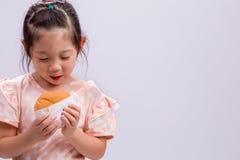Little Girl Eating Hamburger on White / Little Girl Eating Hamburger / Little Girl Eating Hamburger, Studio Shot Stock Photos