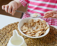 Little girl eating healthy breakfast. Flakes with milk Royalty Free Stock Image