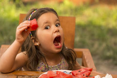 Little girl eating healthy snack. Happy expressive little girl eating watermelon Royalty Free Stock Image