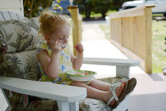 Little girl eating by herself a nutritious snack Stock Photos